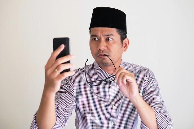 Azjatycki mężczyzna gryzie okulary, patrząc na telefon komórkowy z gniewnym wyrazem twarzy