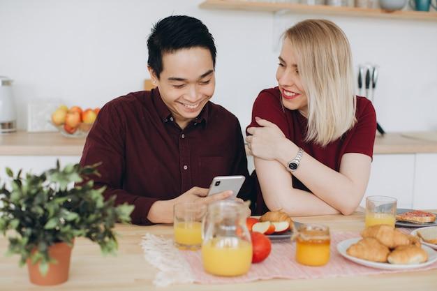 Azjatycki mężczyzna i jego kaukaska blondynki kobieta je śniadanie. wspólnie spędzają czas w kuchni i oglądają wideo przez telefon.