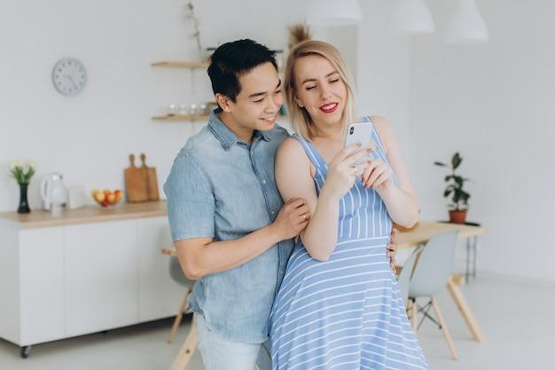 Azjatycki mężczyzna i jego kaukaska blondynki kobieta spędzają razem czas w kuchni i patrząc na telefon