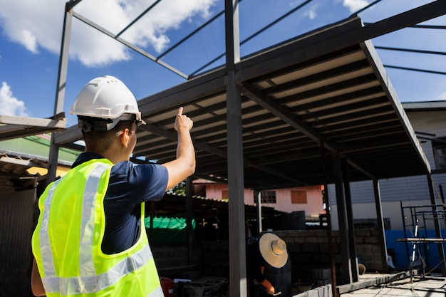 Azjatycki mężczyzna i kobieta inżynier budownictwa papierowego architekta budynku na sobie biały hełm ochronny spojrzeć na budowę.