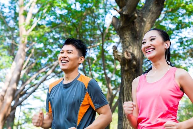 Azjatycki mężczyzna i kobieta jogging w parku miejskim