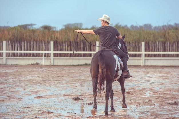Azjatycki mężczyzna jedzie konia przy gospodarstwem rolnym
