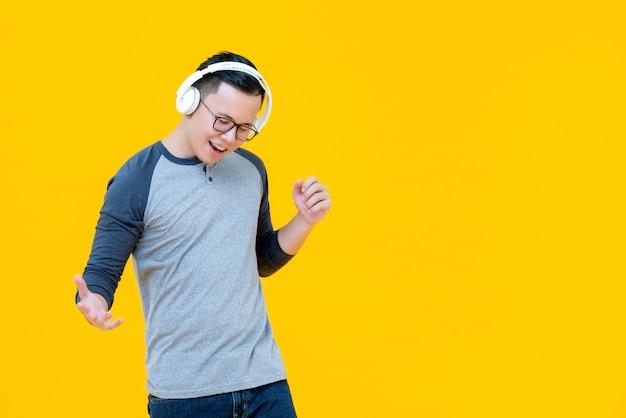 Azjatycki mężczyzna jest ubranym hełmofony słucha muzyka i poruszający ciało