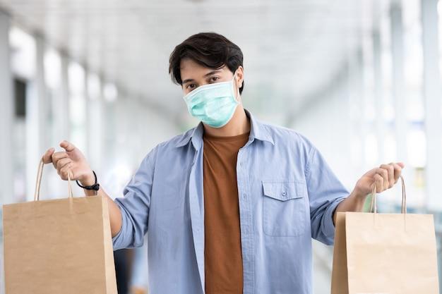 Azjatycki mężczyzna jest ubranym ochronną twarzy maskę trzyma torba na zakupy