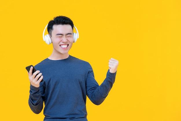 Azjatycki mężczyzna jest ubranym słuchawki słucha jego ulubione piosenki