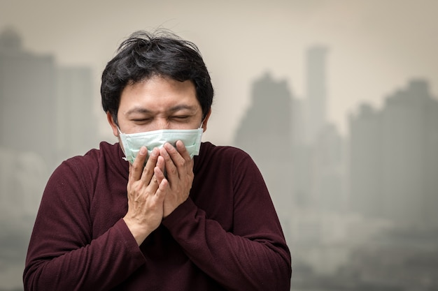 Azjatycki mężczyzna jest ubranym twarzy maskę przeciw zanieczyszczeniu powietrza z kaszleniem