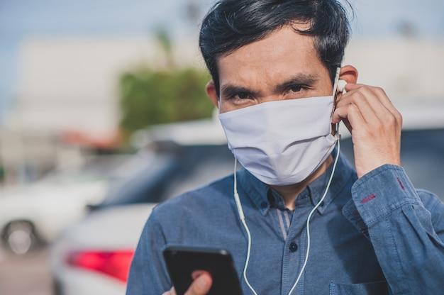Azjatycki mężczyzna jest wywoławczy telefon używać twarzy maskę w mieście