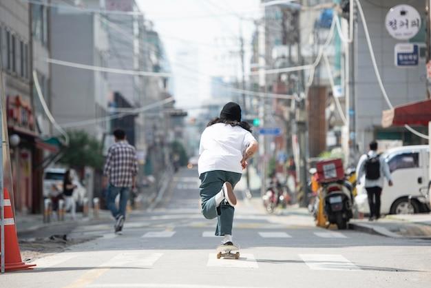 Azjatycki mężczyzna jeździ na deskorolce na zewnątrz