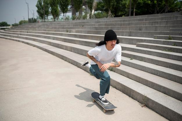 Azjatycki mężczyzna jeździ na deskorolce w mieście na zewnątrz
