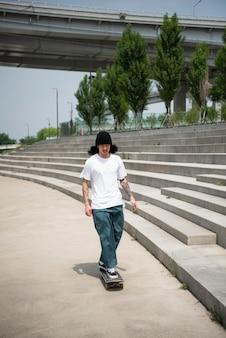 Azjatycki mężczyzna jeździ na deskorolce w mieście
