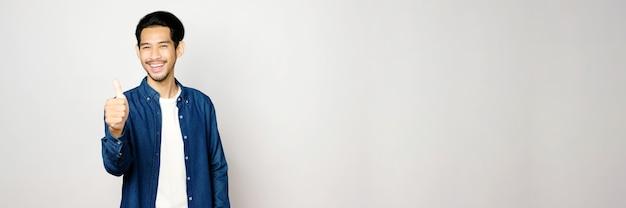 Azjatycki mężczyzna kciuk w górę i uśmiech stojąc na szarym tle