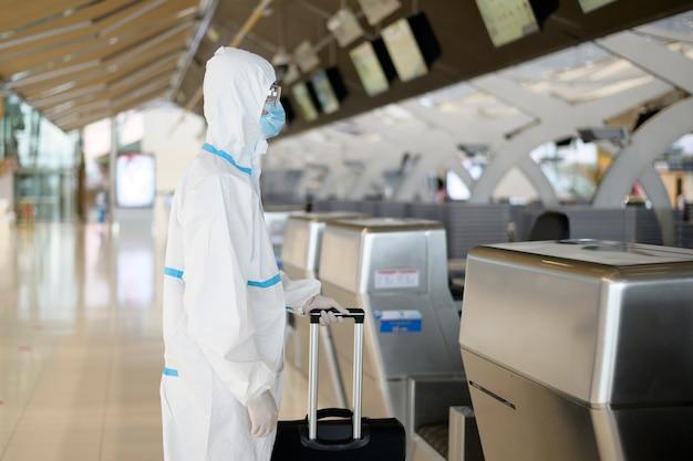 Azjatycki mężczyzna ma na sobie garnitur ppe na lotnisku międzynarodowym, podróż bezpieczeństwa, ochrona covid-19, koncepcja dystansu społecznego.