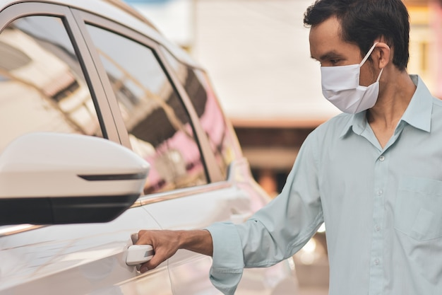 Azjatycki mężczyzna ma na sobie maskę podczas otwierania samochodu