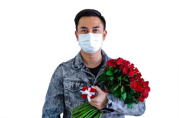 Azjatycki mężczyzna ma na sobie maskę trzymając czerwone róże i pudełko na walentynki koncepcja.