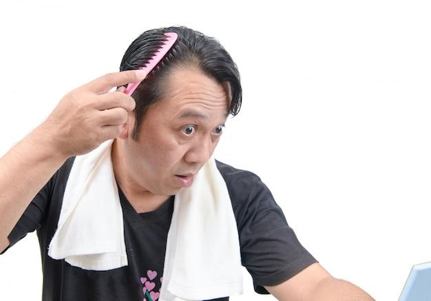 Azjatycki mężczyzna martwi się o jego wypadanie włosów lub łysienie na białym tle
