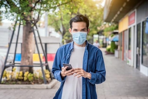 Azjatycki mężczyzna nosi maskę na twarzy trzymając telefon komórkowy styl życia nowy normalny dystans społeczny