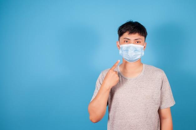 Azjatycki mężczyzna nosi maskę ochronną wirusa drobnoustrojów na niebieskim tle, koncepcja epidemii medycznej koronawirusa covid-19, miejsce
