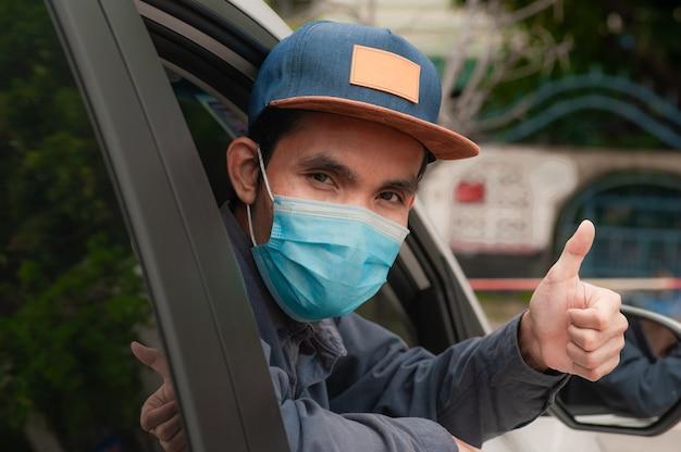 Azjatycki mężczyzna nosić maskę w samochodzie