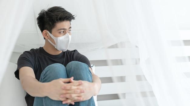 Azjatycki mężczyzna noszący maskę na twarz, aby chronić mdłości i kaszel z powodu koronawirusa covid-19 w pokoju kwarantanny