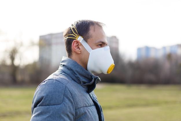 Azjatycki mężczyzna noszący maskę na twarz z powodu zanieczyszczenia powietrza — młody dorosły w parku z maską przeciw zanieczyszczeniom — osoba chroniąca przed zanieczyszczeniem powietrza lub koronawirusem lub covid-19 przez noszenie maski.