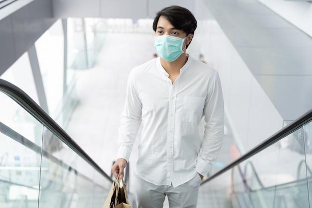Azjatycki mężczyzna noszenie maski medyczne trzymając torbę na zakupy
