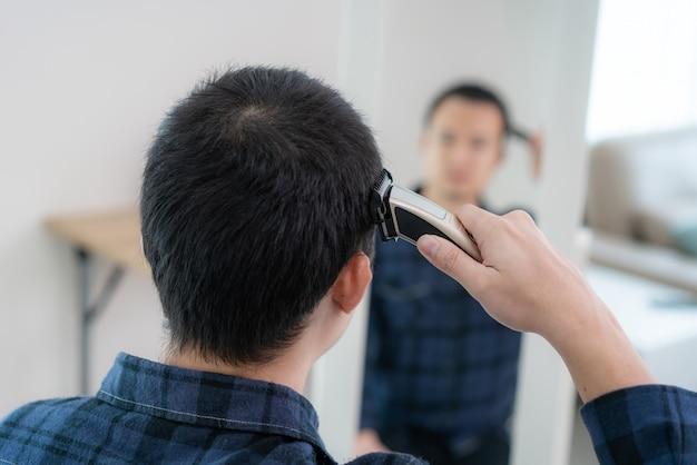 Azjatycki mężczyzna obcinający włosy nożyczkami do strzyżenia w domu zostaje w domu i schronia się w miejscu podczas izolacji domowej przed nowatorskim koronawirusem lub covid-19