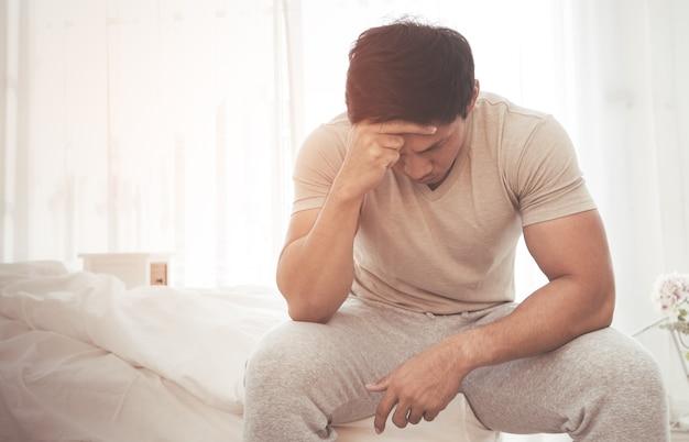 Azjatycki mężczyzna obudził się na łóżku z bólem głowy i stresem