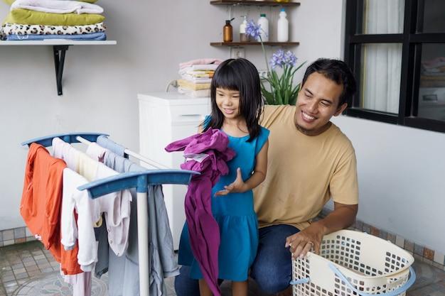 Azjatycki mężczyzna ojciec gospodarstwa domowego i córka dziecko w praniu, suszenie odzieży