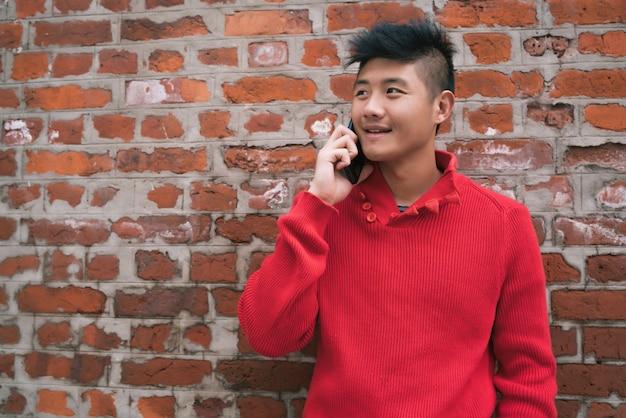 Azjatycki mężczyzna opowiada na telefonie outdoors.