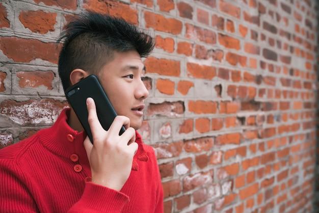 Azjatycki mężczyzna opowiada na telefonie outdoors