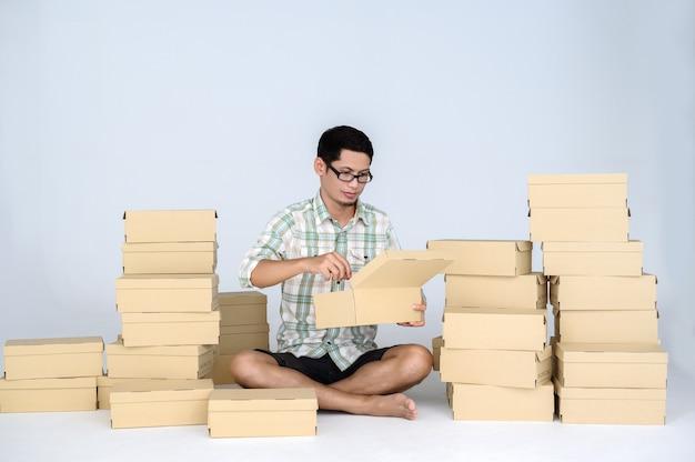 Azjatycki mężczyzna pakujący towary do sprzedaży online wśród wielu pudełek z paczkami. koncepcja niezależnego uruchamiania i domowego biura firmy online.