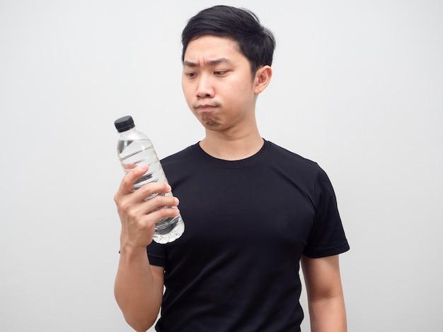 Azjatycki mężczyzna patrzący na butelkę wody w ręku i czujący wahanie na białym tle