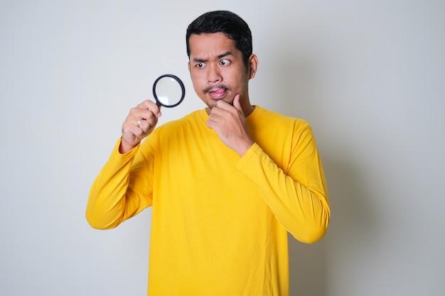 Azjatycki mężczyzna patrzący na coś za pomocą szkła powiększającego z ciekawym wyrazem twarzy