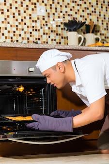 Azjatycki mężczyzna pieczenia tort w domowej kuchni