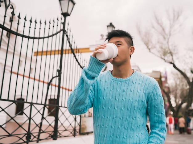 Azjatycki mężczyzna pije filiżankę kawy.