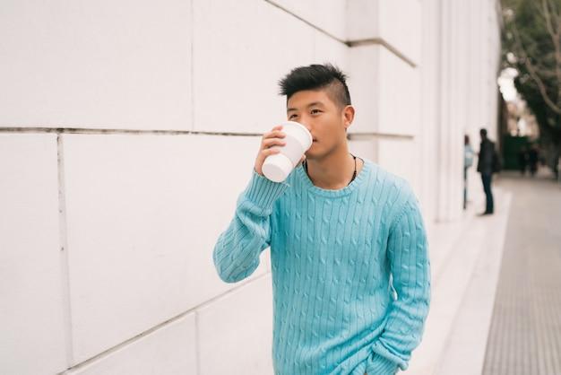 Azjatycki mężczyzna pije filiżankę kawy