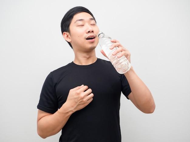 Azjatycki mężczyzna pije wodę z butelki na białym tle