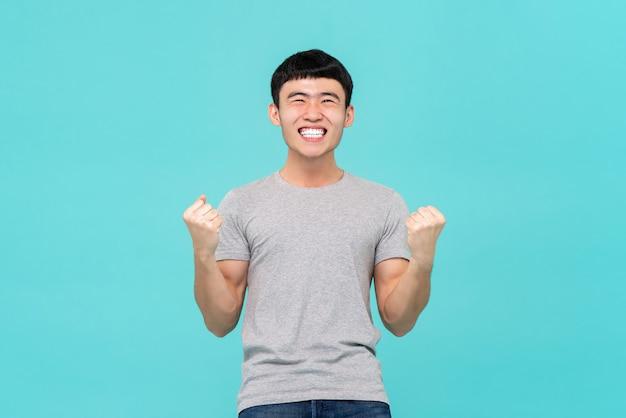 Azjatycki mężczyzna podnosi jego pięści robi tak gestowi