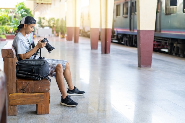 Azjatycki mężczyzna podróżnik z mienia aparatem fotograficznym i plecakiem przy dworcem