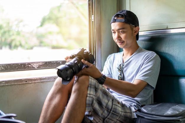 Azjatycki mężczyzna podróżnik z ręki trzymającej aparat fotograficzny i plecak