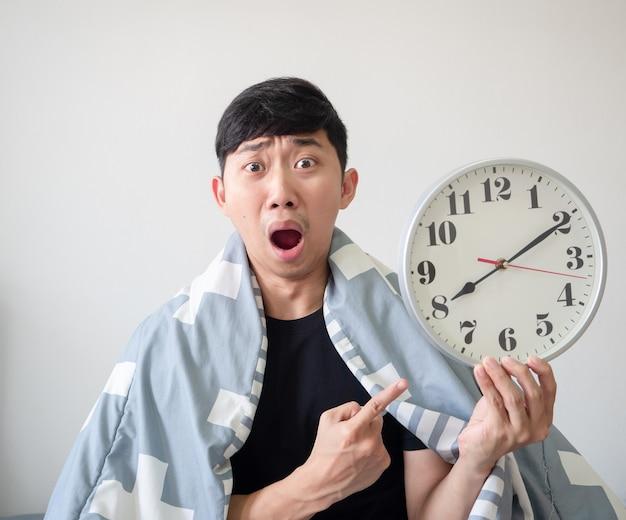 Azjatycki mężczyzna pokrywa koc punkt na zegarze w ręku z zszokowaną twarzą późną koncepcją na białym tle