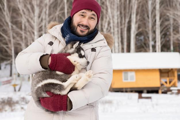 Azjatycki mężczyzna pozuje z szczeniakiem w zimie
