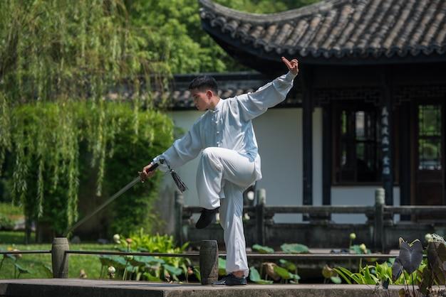 Azjatycki mężczyzna pracujący z mieczem tai chi rano w parku, chińskie sztuki walki