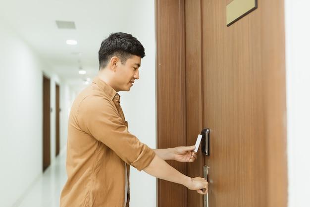 Azjatycki mężczyzna ręka trzyma kartę dostępu / kartę klucza elektroniczna kontrola dostępu do drzwi skanowanie w celu zablokowania i odblokowania drzwi