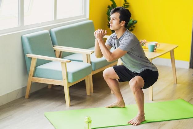 Azjatycki mężczyzna robi ćwiczenia w domu