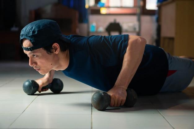 Azjatycki mężczyzna robi sprawności fizycznej ćwiczy z pcha up w domu