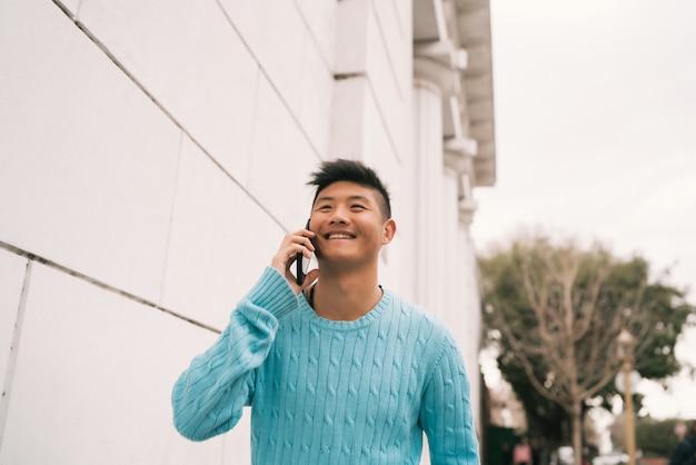 Azjatycki mężczyzna rozmawia przez telefon na zewnątrz.