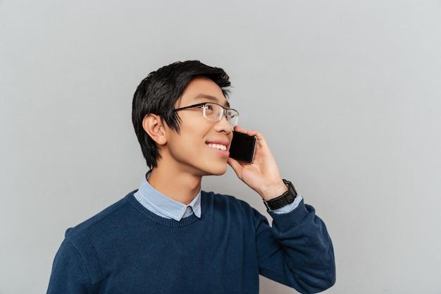 Azjatycki mężczyzna rozmawia przez telefon. z okularami