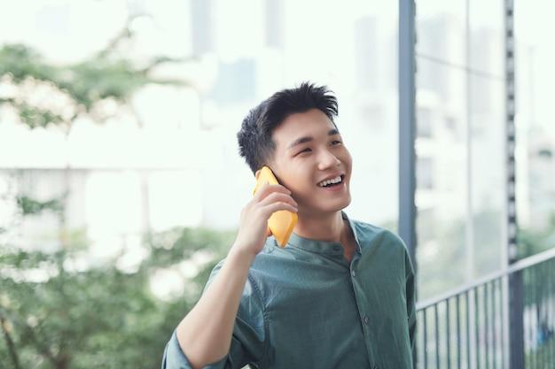 Azjatycki mężczyzna rozmawiający na smartfonie uśmiechnięty śmiejący się głośno relaksujący się na balkonie