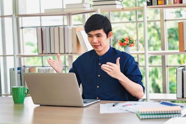 Azjatycki mężczyzna rozmowa wideo z laptopem w biurze